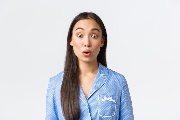 Close-up van geschrokken en geschokt aziatisch meisje in blauwe pyjama die iets verbazingwekkends ziet, kijkt met ontzag en zegt wow, verbaasd starend naar de camera op een witte achtergrond