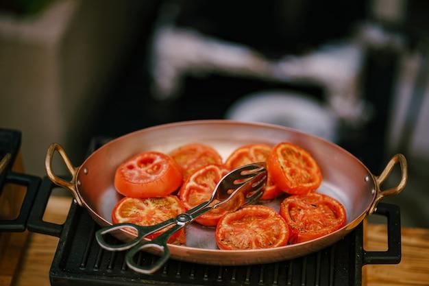 Close-up van gesneden gebraden tomaten in een pan op een gietijzerfornuis