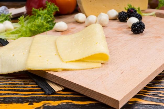Close up van gesneden kaas op houten snijplank gegarneerd met bramen en bocconcini en geserveerd op houten tafel
