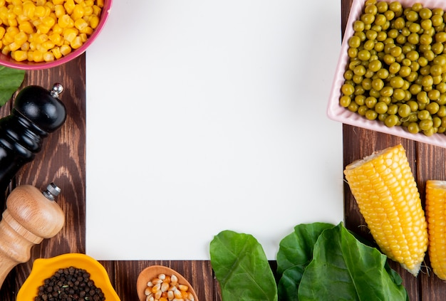 Close-up van gesneden maïs met maïs zaden zwarte peper zaden groene erwten spinazie en notitieblok op houten oppervlak met kopie ruimte