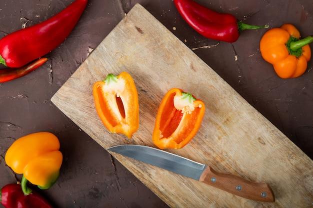 Close-up van gesneden peper op houten oppervlak met mes en paprika op kastanjebruine achtergrond