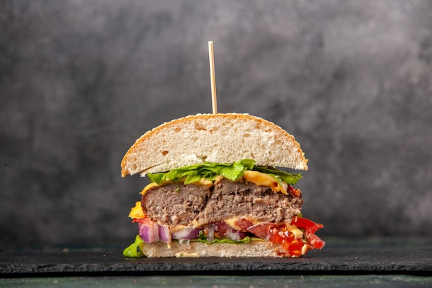 Close-up van gesneden smakelijke sandwiches op zwarte lade op donkere mix kleur oppervlak