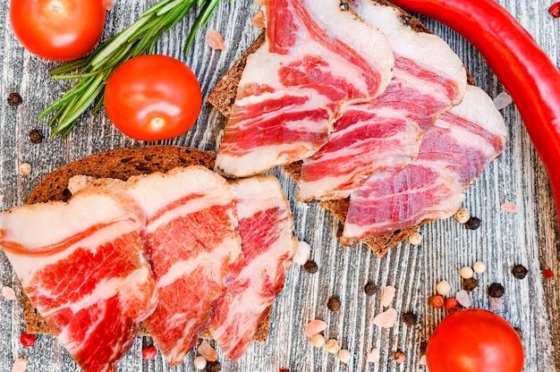 Close-up van gesneden spek sandwitches op de houten tafel