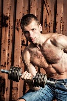 Close up van gespierde jonge man tillen gewichten op metalen achtergrond