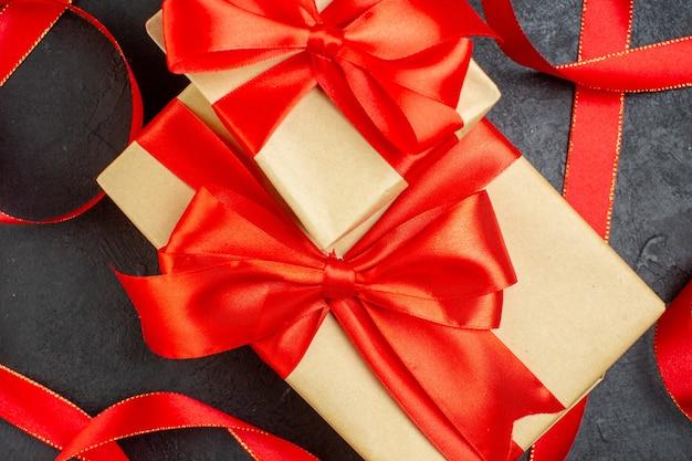 Close-up van gestapelde mooie geschenken met rood lint op donkere achtergrond