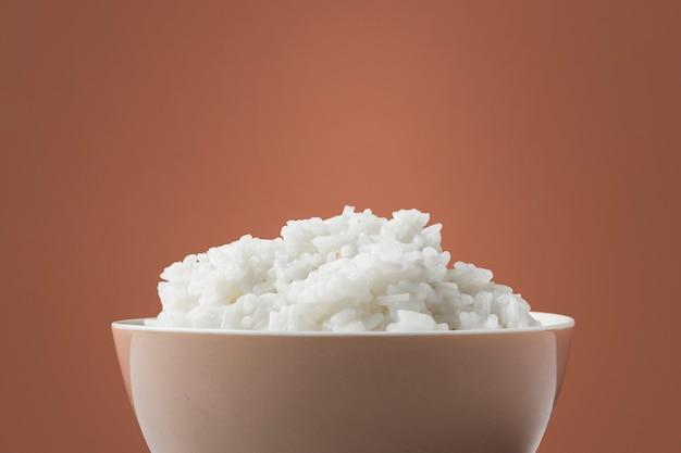 Close-up van gestoomde witte rijst in kom tegen bruine achtergrond