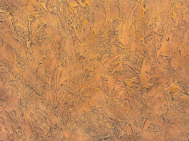 Close-up van getextureerde gips in gouden kleuren. modern interieur. reliëftextuur van stopverf.