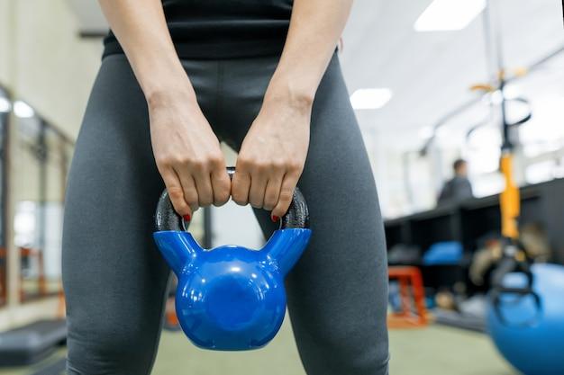 Close-up van gewicht in de handen van een sportieve vrouw
