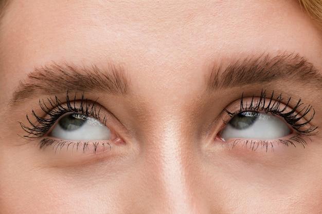 Close up van gezicht van mooie blanke jonge vrouw focus op ogen menselijke emoties