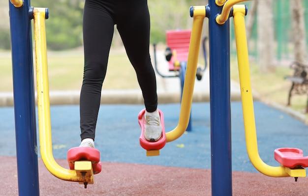 Close-up van gezonde jonge aziatische vrouw in sportkleding ontspannen op openbare oefening machine buiten.