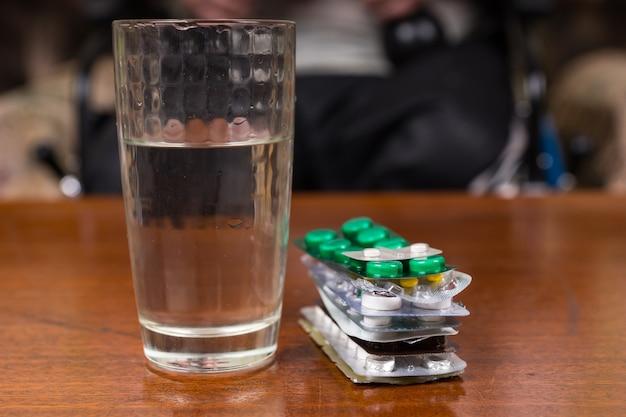Close up van glas water op tafel naast stapel van verschillende pillen en tabletten in folie blisterverpakkingen
