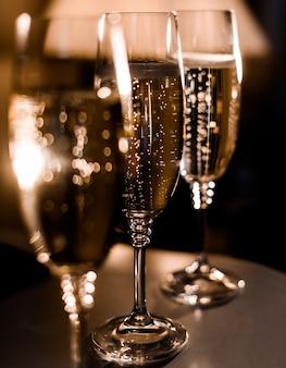 Close-up van glazen met champagne op de donkere lichte achtergrond
