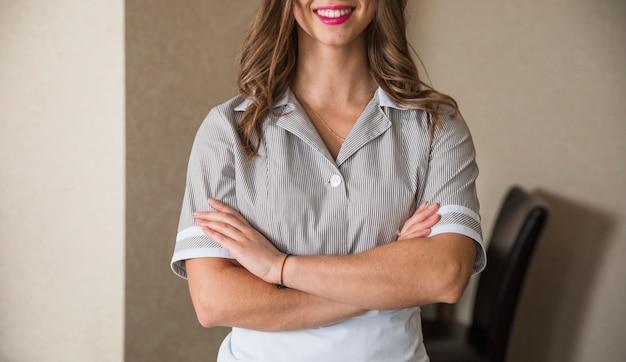 Close-up van glimlachend kamermeisje dat zich met haar gekruiste wapens bevindt