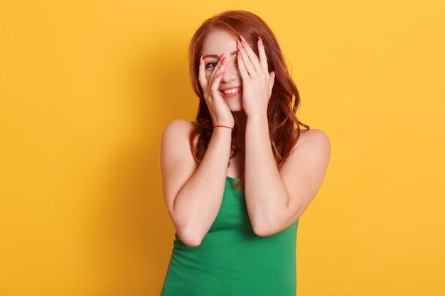 Close-up van glimlachend meisje met rood haar, gezicht bedekken met handpalmen, breed lachend en verstoppertje spelen, kijkend door vingers, staat over gele achtergrond.