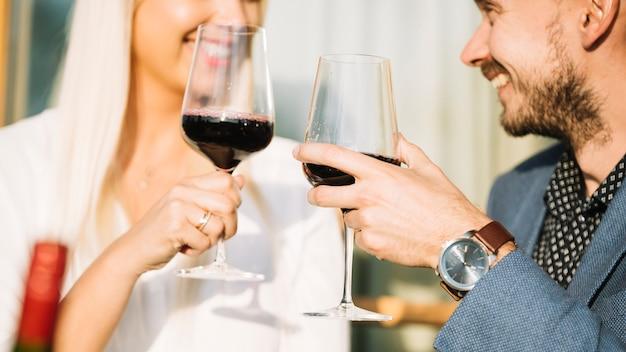 Close-up van glimlachend paar die rode wijnglazen roosteren