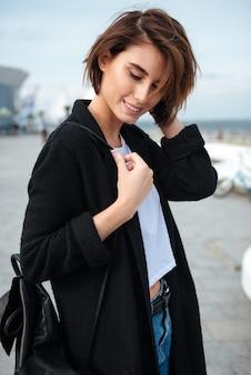 Close-up van glimlachende aantrekkelijke jonge vrouw met rugzak die zich in openlucht bevindt