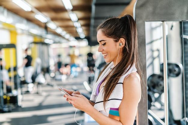 Close-up van glimlachende blanke vrouw die muziek op slimme telefoon kiest terwijl ze in een sportschool staat. handdoek om de nek.