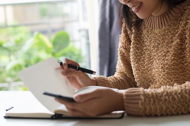 Close-up van glimlachende dame die haar nota's in agenda lezen