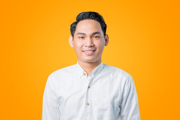 Close-up van glimlachende jonge aziatische man die een wit overhemd draagt