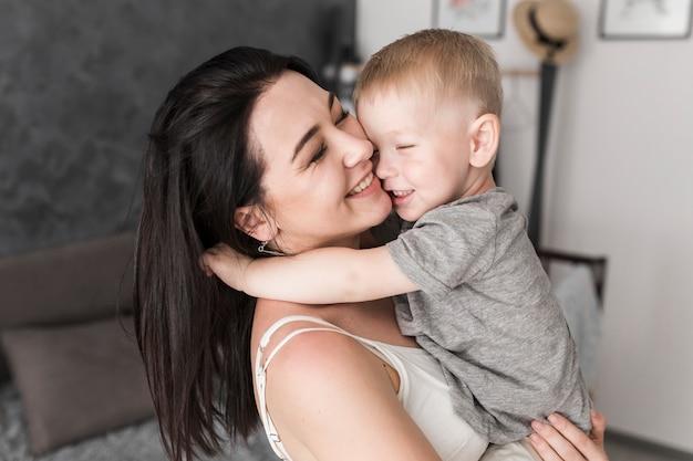 Close-up van glimlachende jonge vrouw die van haar zoon houdt