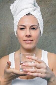 Close-up van glimlachende jonge vrouw met een handdoek over haar die een glas schoon water over een betegelde muurachtergrond houden. gezondheid en schoonheidsconcept.