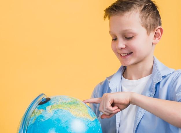 Close-up van glimlachende jongen wat betreft de bol met vinger tegen gele achtergrond