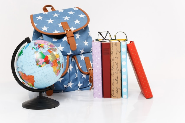 Close up van globe, blauwe rugzak met sterrenprint en kleurrijke schoolboeken Gratis Foto