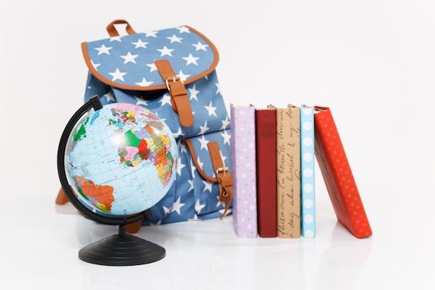 Close up van globe, blauwe rugzak met sterrenprint en kleurrijke schoolboeken
