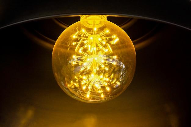 Close-up van gloeilamp schijnt, geel licht van de lamp hangen op het plafond