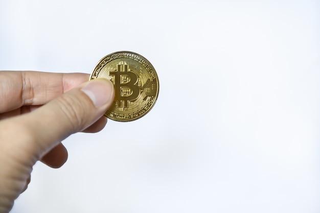 Close-up van gouden bitcoin-munt op mandhand op witte achtergrond.