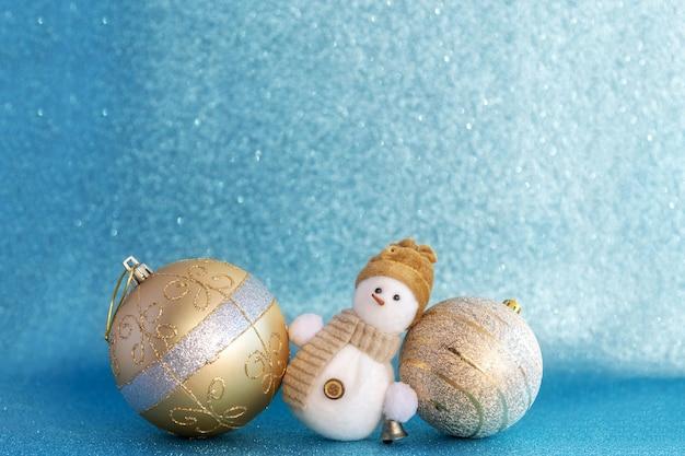 Close-up van gouden kerstballen en sneeuwpop ligt op blauwe bokeh licht achtergrond