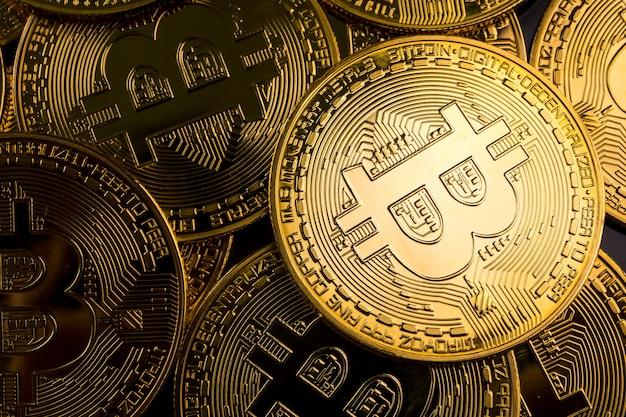 Close up van gouden munten met bitcoin symbool achtergrond.