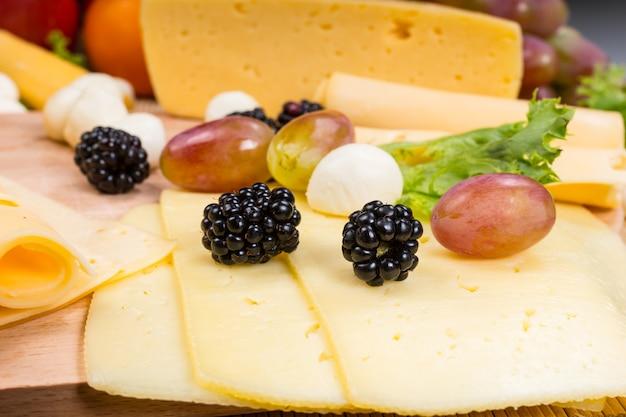 Close up van gourmet cheese board - detail van gesneden kaas gegarneerd met vers fruit en bocconcini
