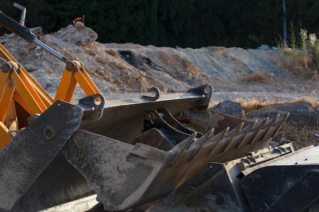 Close up van graafmachine emmer. gravende machineonderdelen, industriedetail van bulldozerschop. bouw gele graafmachine vuile emmer tanden. graafwerktuigemmer die op bouwwerf rusten