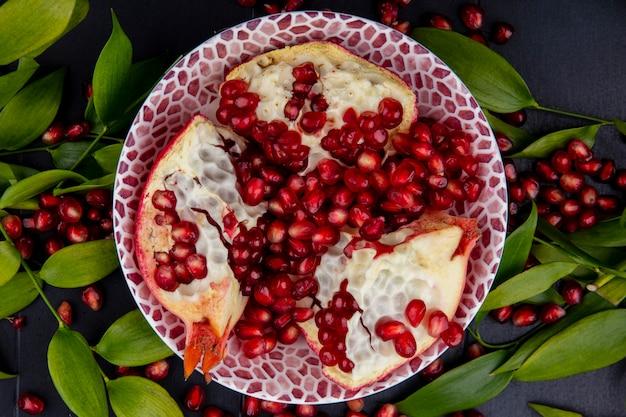 Close-up van granaatappelstukken in kom met bessen en bladeren op zwarte oppervlakte