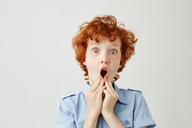 Close up van grappig langs met krullend gember haar en sproeten hand in hand in de buurt van mond, wordt geschokt
