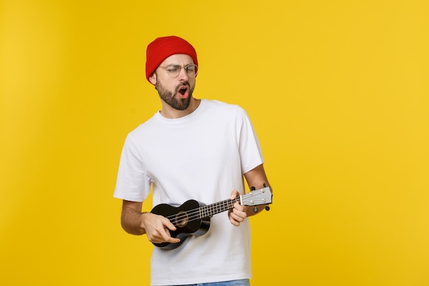 Close-up van grappige jonge man een gitaar spelen. geïsoleerd op geel goud
