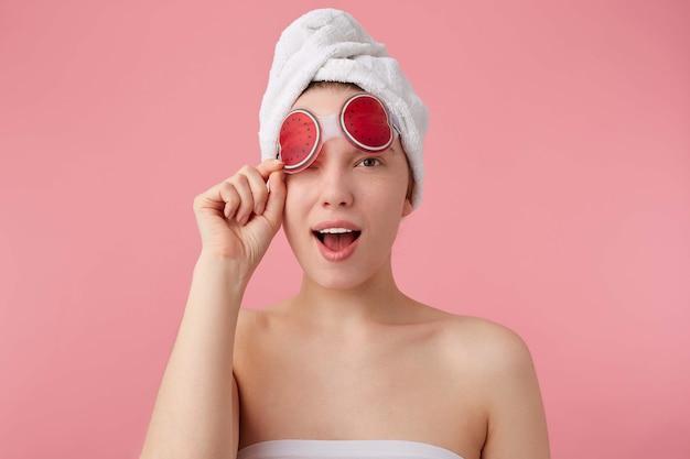 Close-up van grappige jongedame met masker voor ogen, na het douchen met een handdoek op haar hoofd, kijkt en knipoogt, staat.