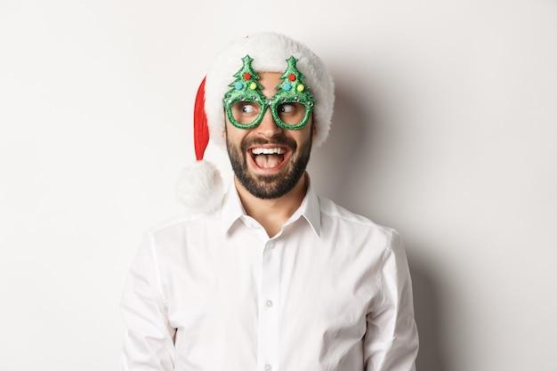 Close-up van grappige man op zoek naar links met verbaasd gezicht, kerstfeest bril en kerstmuts, nieuwjaar vieren