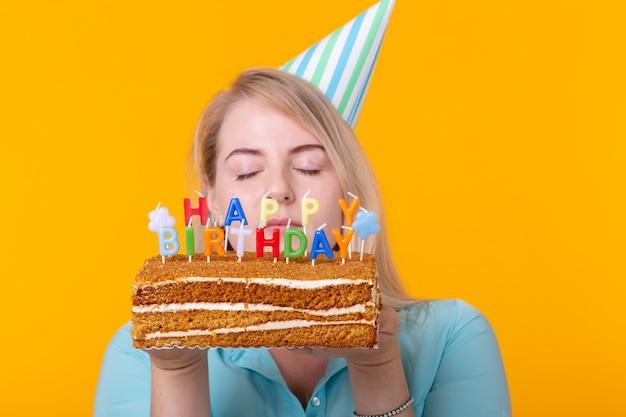 Close-up van grappige positieve jonge vrouw houdt in haar handen een zelfgemaakte cake met de inscriptie gelukkige verjaardag poseren op een gele muur. concept van vakanties en jubilea.