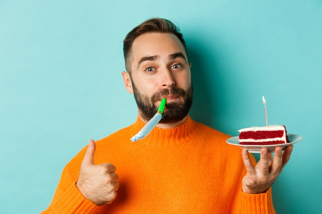 Close-up van grappige volwassen man die zijn verjaardag viert, bday cake met kaars houdt, partij wistle blaast en duim-up toont, staande over lichtblauwe achtergrond.