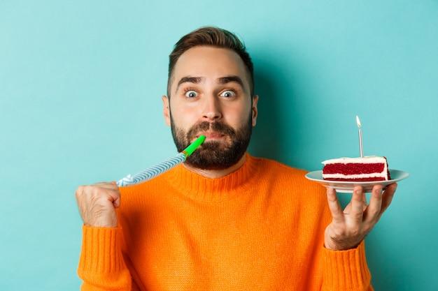 Close-up van grappige volwassen man die zijn verjaardag viert, bday cake met kaars houdt, partij wistle blaast en zich verheugt, staande over lichtblauwe achtergrond.