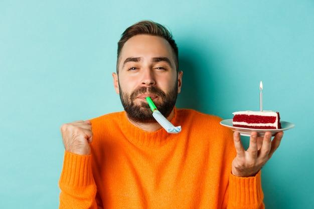 Close-up van grappige volwassen man viert zijn verjaardag, verjaardagstaart met kaars te houden