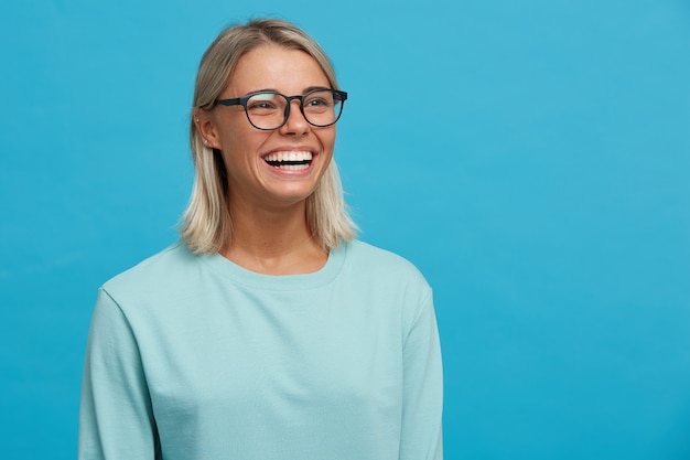 Close up van grappige vrolijke blije blonde jonge vrouw in glazen met brede glimlach