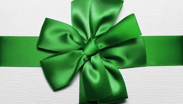 Close-up van groen inwikkeling lint in vorm van boog voor witte geschenkdoos.