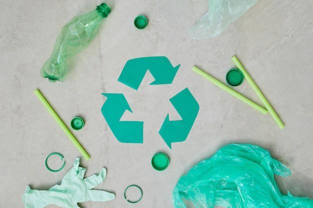 Close-up van groen recyclingsymbool met plastic flessen en zakken die op grijze achtergrond worden geïsoleerd
