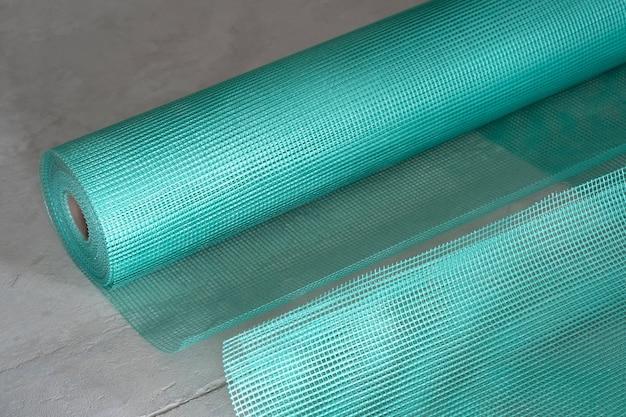 Close-up van groenachtig blauw versterkend gaas opgerold.