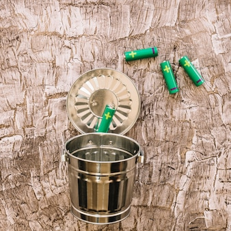 Close-up van groene batterijen over metalen vuilnisbak