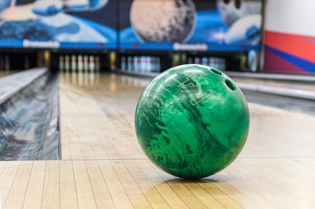 Close-up van groene bowlingbal tegen lege rijstroken in de bowlingbaan