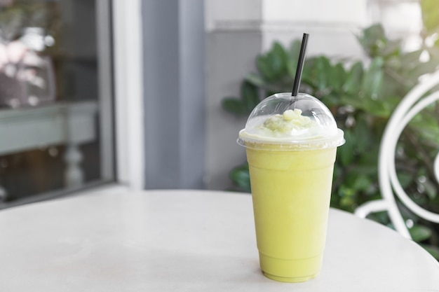 Close-up van groene thee matcha smoothies in een plastic beker.
